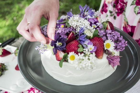 Erdbeer-Torte mit Blumen und frischen Erdbeeren dekorieren